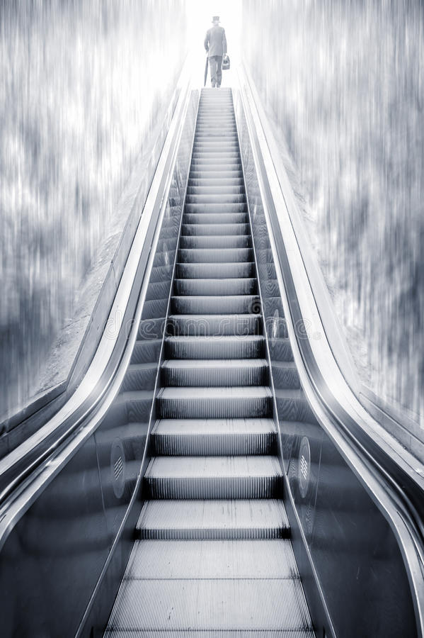 Escalera móvil futurista entre cascadas y un hombre en el top, con referencia a fotografía de archivo