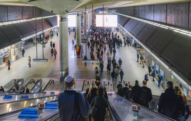 Escalera móvil hacia la estación del metro de Canary Wharf con los viajeros en la hora punta en Londres, Inglaterra, Reino Unido  fotos de archivo