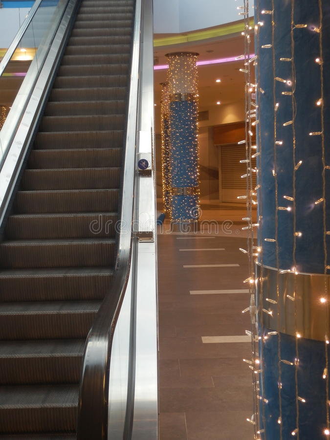 Escalera móvil y pilares adornados de la ayuda foto de archivo libre de regalías
