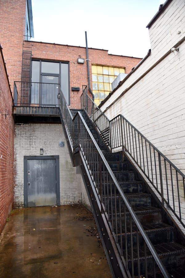 Escalera negra a la entrada trasera imagenes de archivo