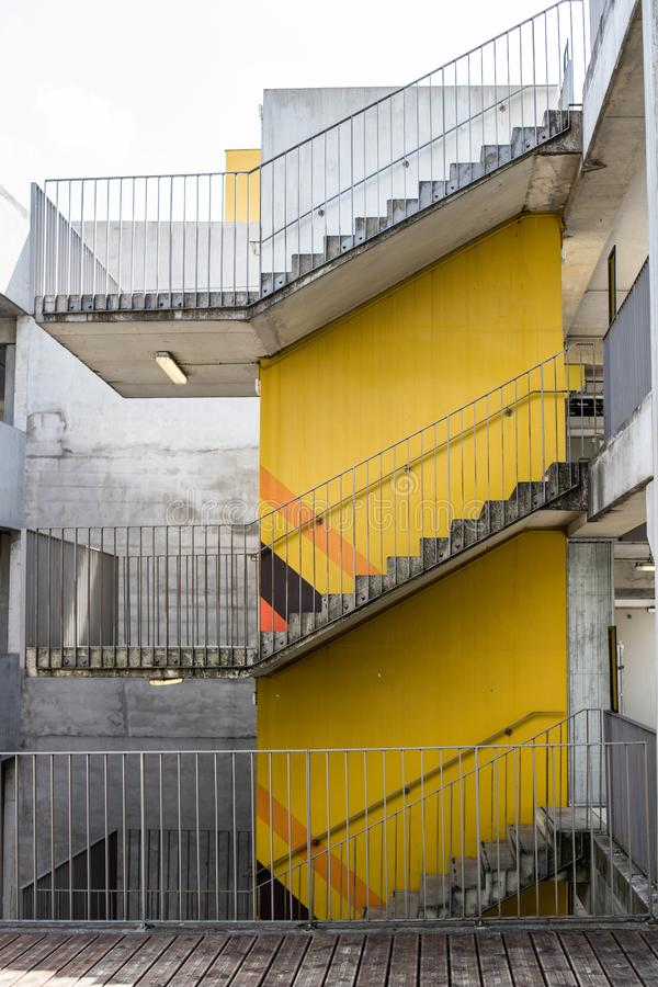 Escalera a tres pisos Muro de cemento amarillo Escalera alrededor de la estructura concreta fotos de archivo