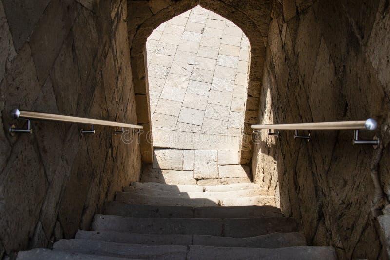 Escaleras abajo de la entrada a través del arco, sombra, pasos fotos de archivo