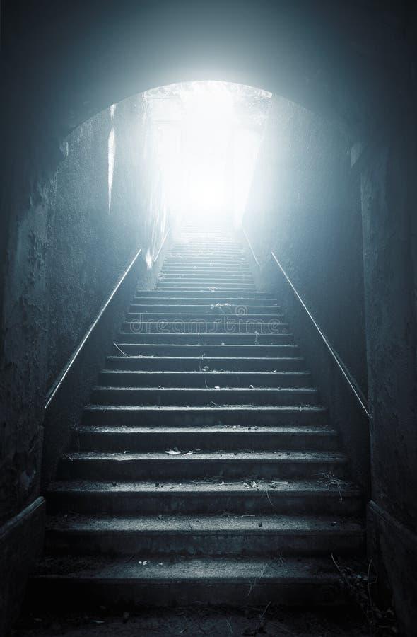 Escaleras abandonadas viejas que suben a la luz foto de archivo