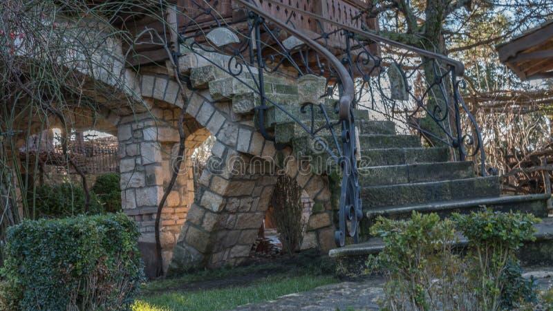 Escaleras al aire libre curvadas de la casa en una casa rural, con la barandilla del hierro labrado fotos de archivo libres de regalías