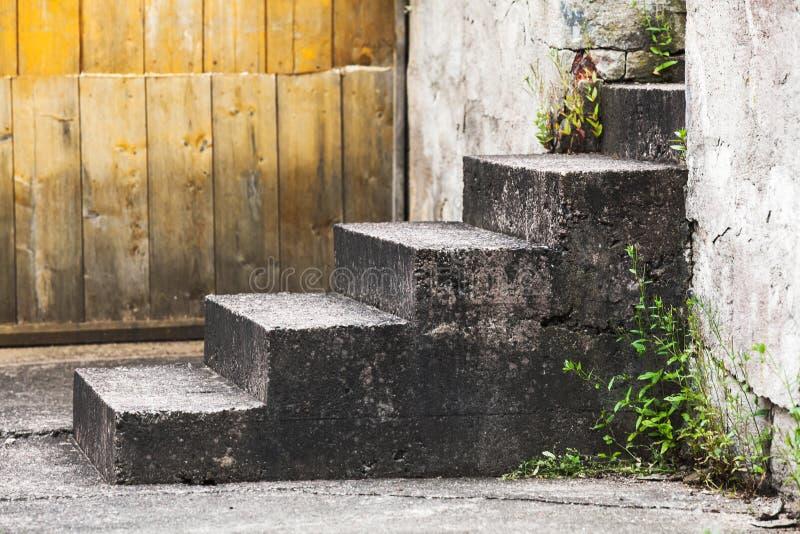 Escaleras concretas viejas cerca de la pared de madera fotos de archivo libres de regalías