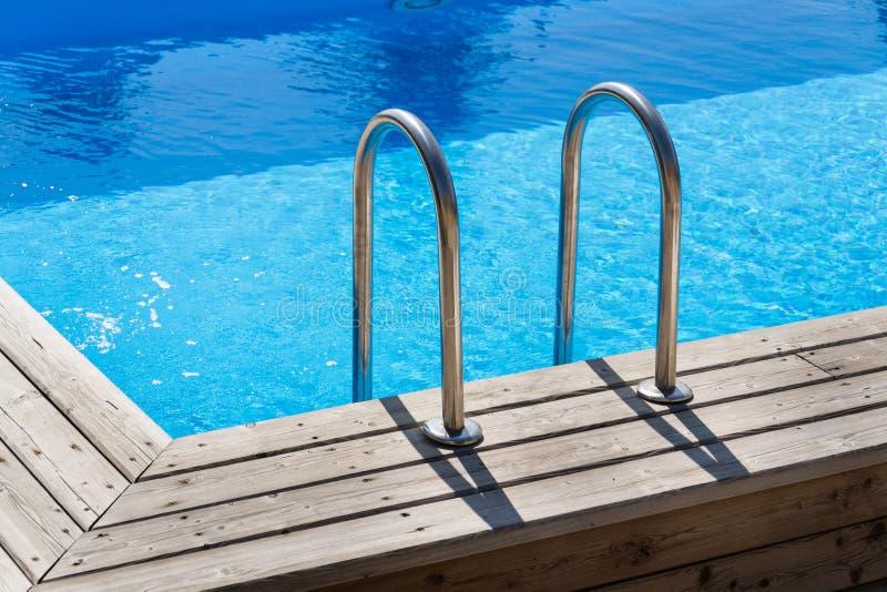 Escaleras de acero de la escalera en la piscina al aire libre azul de la desnatadora, piso de madera imagen de archivo
