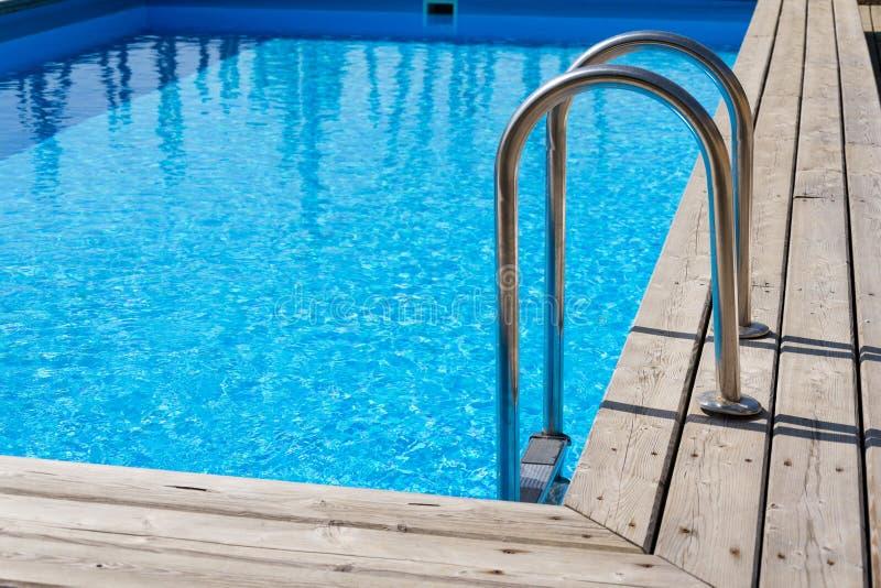 Escaleras de acero de la escalera en la piscina al aire libre azul de la desnatadora, piso de madera foto de archivo