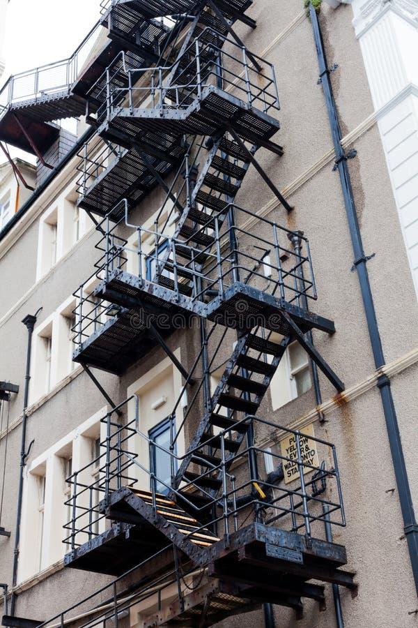 Escaleras de la salida de incendios del metal Escaleras de la salida de incendios detrás de un edificio Escaleras en la parte de  foto de archivo libre de regalías