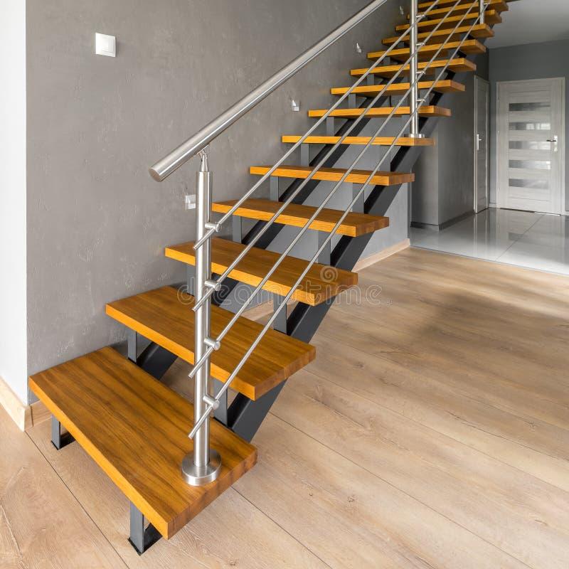 Escaleras de madera con la verja de plata foto de archivo