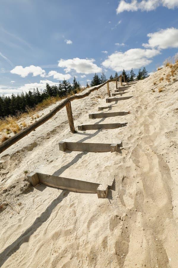Escaleras de madera de la trayectoria en la arena hasta el cielo azul fotos de archivo