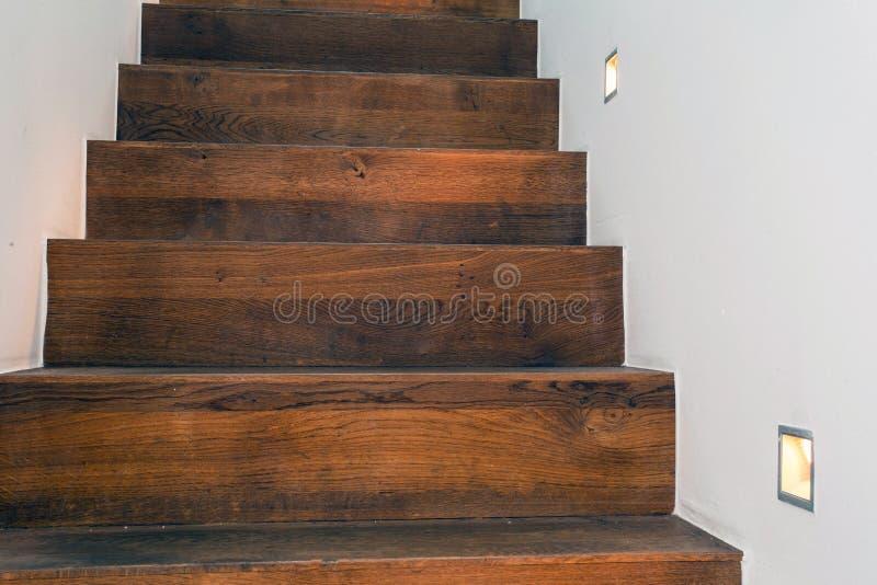 Escaleras de madera por noche con la luz llevada en el diseño moderno de la pared blanca imágenes de archivo libres de regalías
