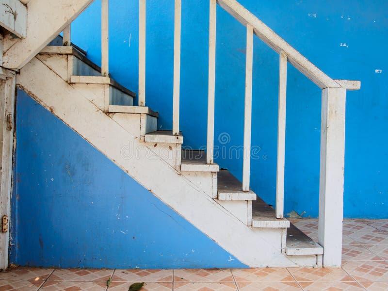 Escaleras de madera y pared azul fotos de archivo
