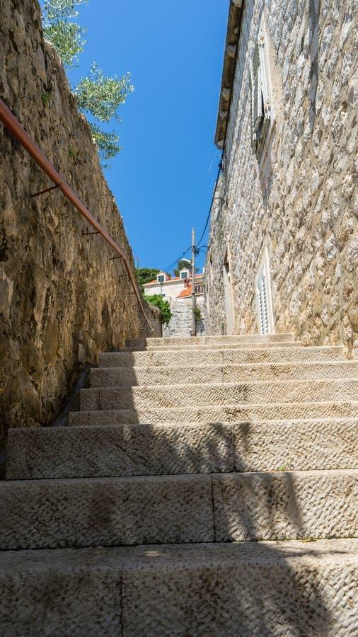 escaleras de piedra estrechas entre la vieja área residencial en Croacia Pueblo adriático de la costa con las casas de piedra y l imagen de archivo libre de regalías
