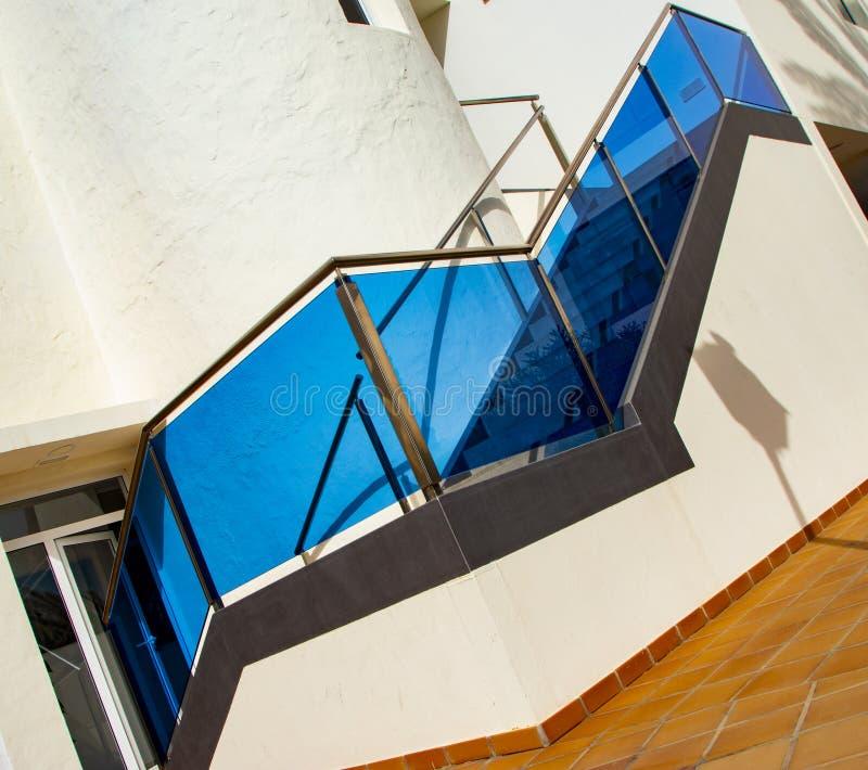 Escaleras de piedra modernas con la verja del acero inoxidable con el vidrio azul imágenes de archivo libres de regalías