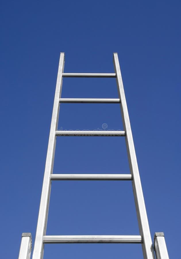 Escaleras del éxito al cielo azul foto de archivo