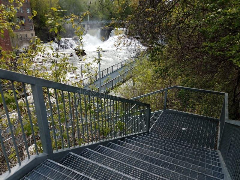 Escaleras metálicas o escalones que descienden hasta el agua y la cascada en Sherbrooke, Canadá imagenes de archivo