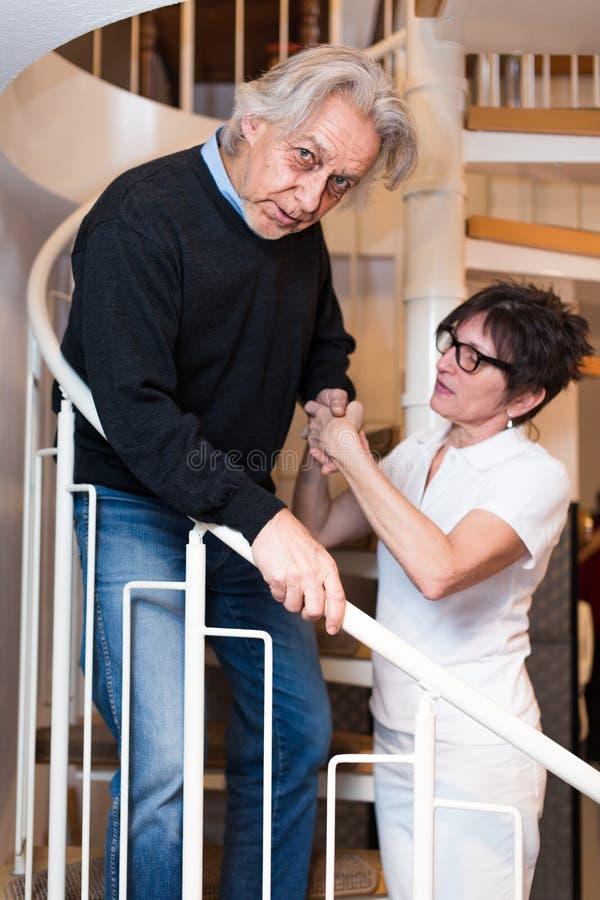Escaleras que suben de Helping Senior Man de la enfermera fotografía de archivo libre de regalías