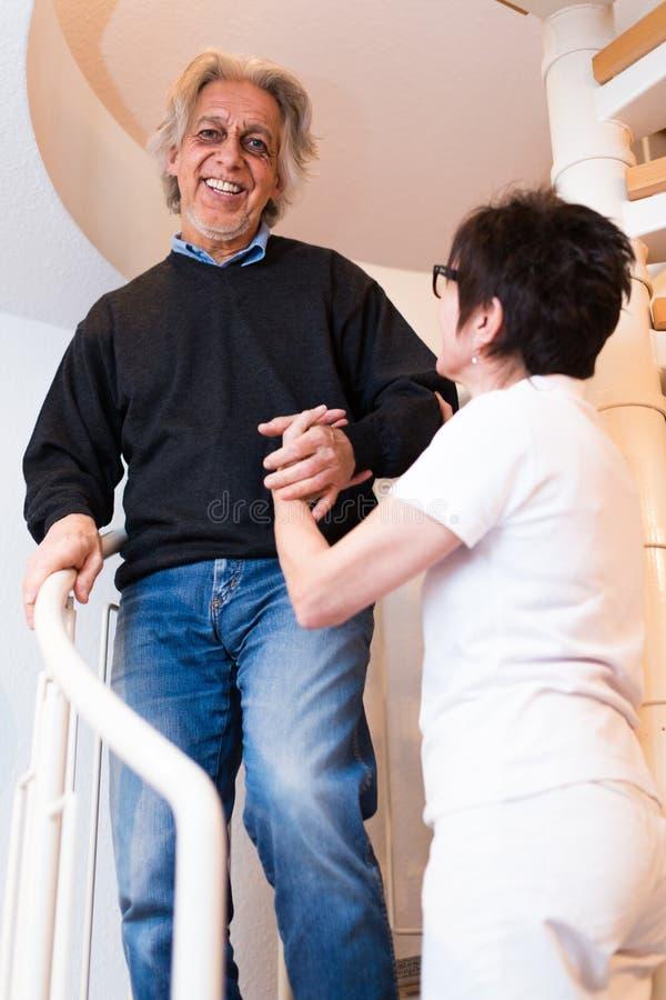 Escaleras que suben de Helping Senior Man de la enfermera foto de archivo