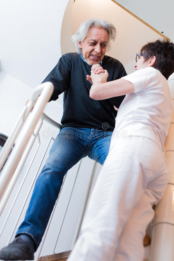 Escaleras que suben de Helping Senior Man de la enfermera imagen de archivo
