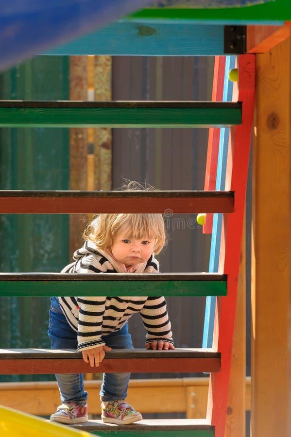 Escaleras que suben de la pequeña niña pequeña linda de una diapositiva de los niños fotos de archivo