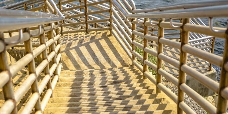 Escaleras que van abajo del océano tranquilo en acantilados de la puesta del sol fotos de archivo libres de regalías