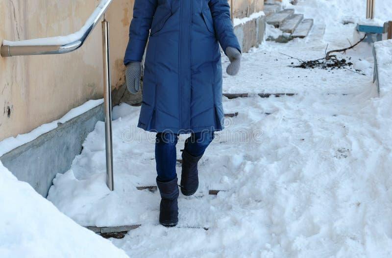 Escaleras resbaladizas Mujer irreconocible en del azul una chaqueta abajo que camina abajo de una escalera nevosa fotos de archivo libres de regalías