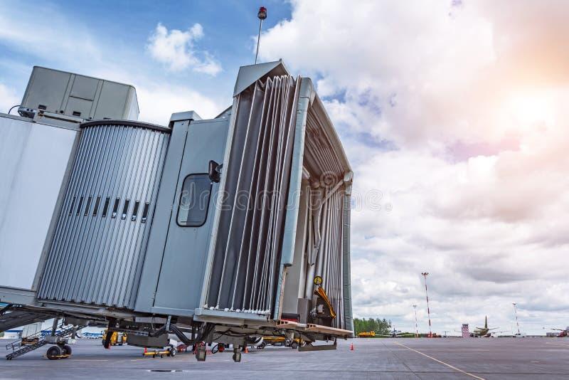 Escaleras telescópicas de la pasarela de la visión ascendente cercana para los pasajeros de embarque en el avión, aparcamiento va foto de archivo libre de regalías
