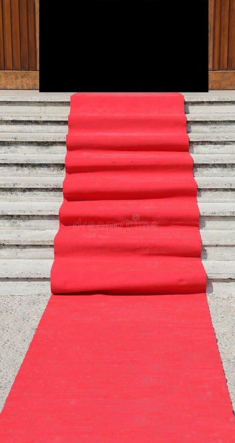 Escalier avec un tapis rouge luxueux vers la porte ouverte photo stock
