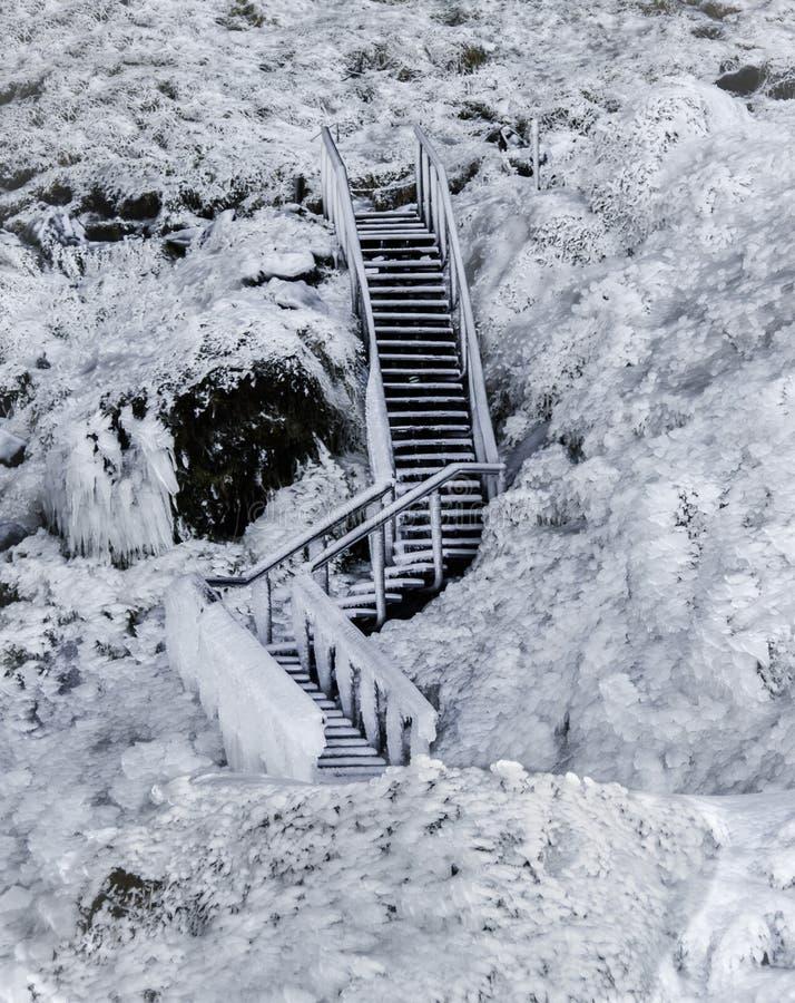 Escalier en bois congelé en glace, couverte de glaçons contre un gisement de lave gelé couvert de la glace et de neige photographie stock