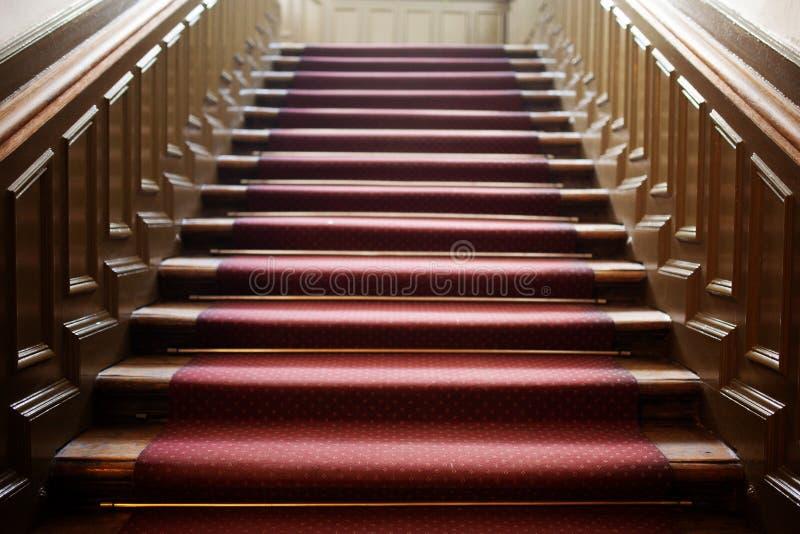 Escalier en bois vide avec le tapis rouge photographie stock