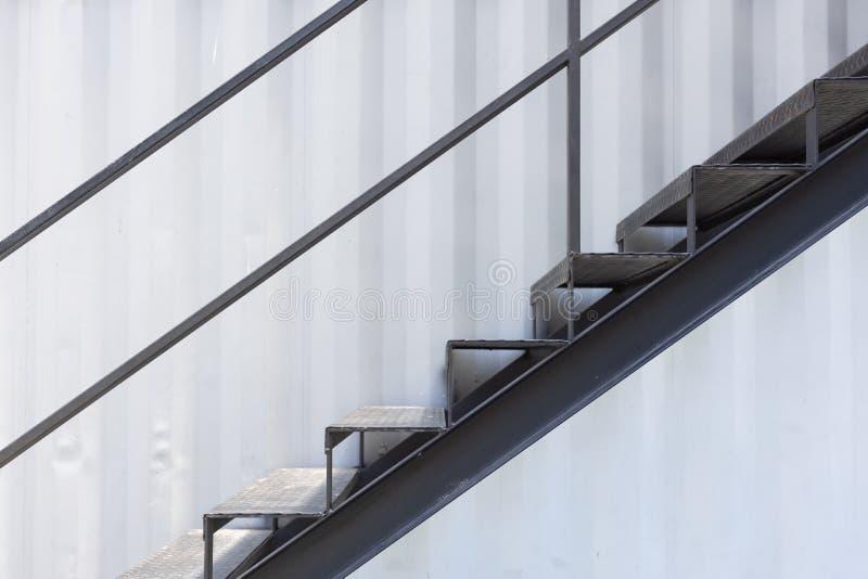 Escalier en métal ou escalier extérieur de sortie de secours avec le fond ondulé de mur de feuille photographie stock libre de droits