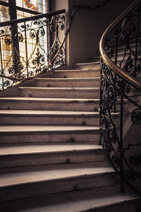 Escalier en pierre en spirale avec les étapes blanches de granit et balustrades avec les modèles forgés en métal images libres de droits