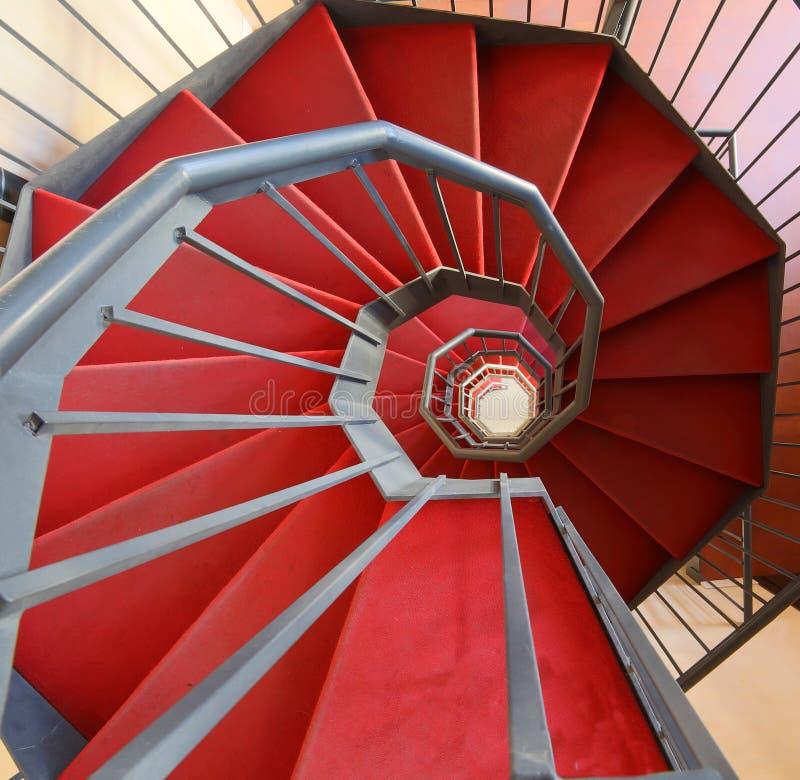 Escalier en spirale avec le tapis rouge dans un bâtiment moderne photo stock