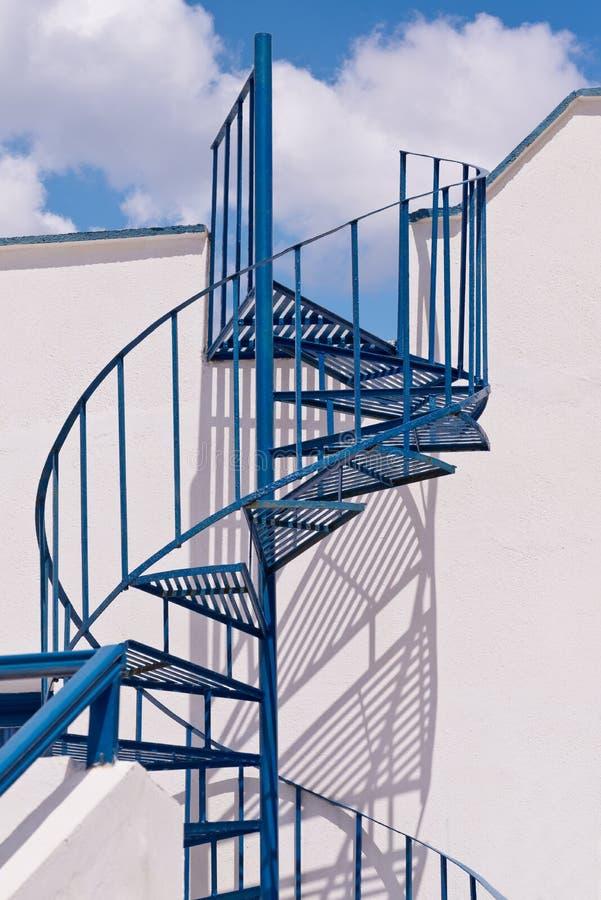 Escalier en spirale bleu de Santorini Grèce, ombres, ciel, nuages photographie stock libre de droits