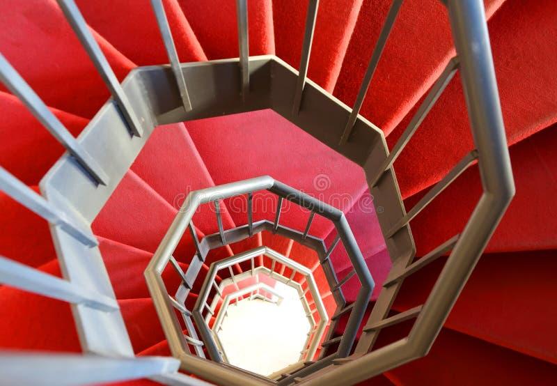 Escalier en spirale moderne avec le tapis rouge photo stock