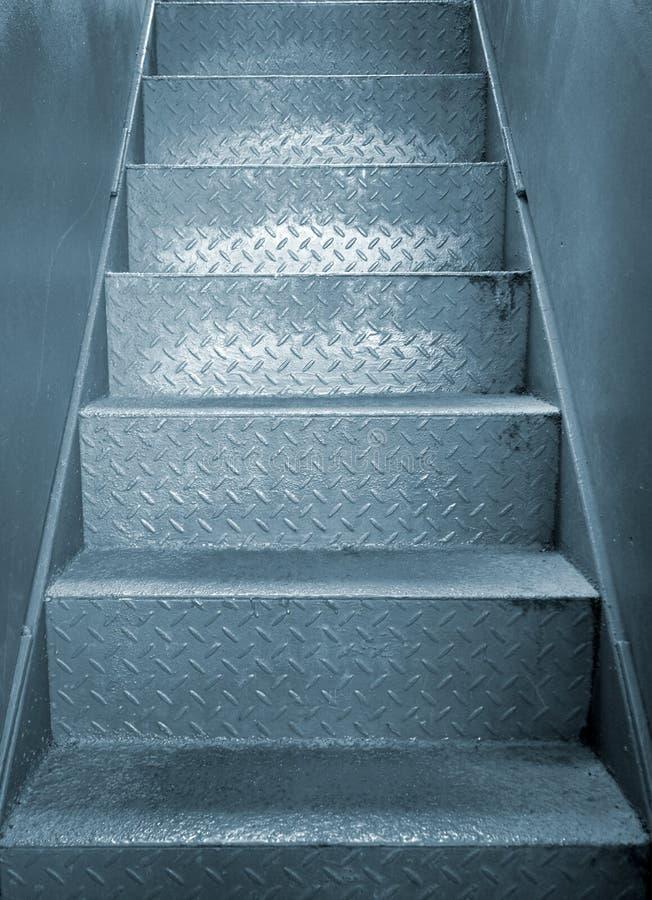 Escalier industriel en acier gris avec la texture modelée approximative de poignée dans un passage entre deux murs de plaque méta photo stock