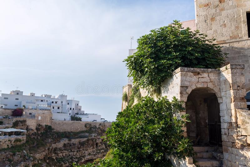 Escaliers avec un passage envahi à la vieille ville au centre historique au-dessus de la belle plage Lama Monachile dans Polignan images stock