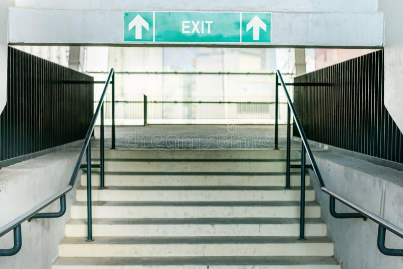 Escaliers de stade et symbole vert de sortie photographie stock libre de droits
