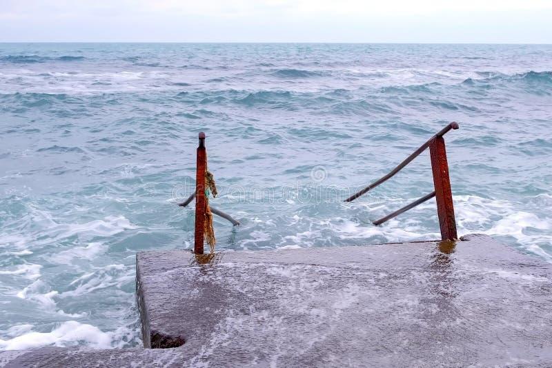 Escaliers entrant dans la mer agitée Mauvais jour à la plage avec de grandes vagues image libre de droits