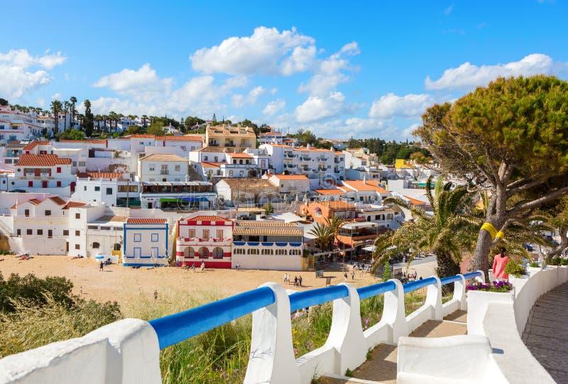 Escaliers menant à la plage sablonneuse entourée par les maisons blanches typiques, Carvoeiro, Algarve, Portugal image stock
