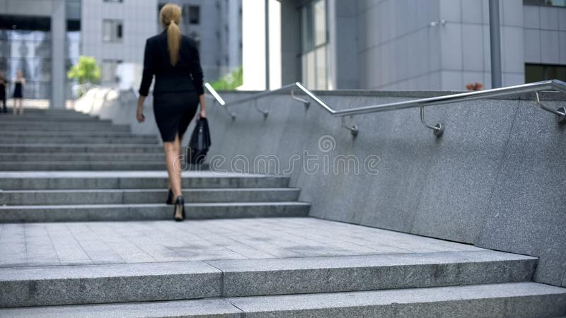 Escaliers s'élevants de dame d'affaires au centre de bureau, échelle de carrière, promotion de succès photographie stock libre de droits