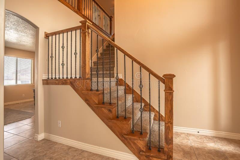 Escaliers tapissés avec la balustrade en bois de balustrade et en métal à l'intérieur d'une nouvelle maison vide photographie stock