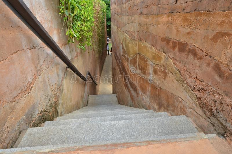 Escaliers vers le bas au plancher entre le haut mur rouge image libre de droits