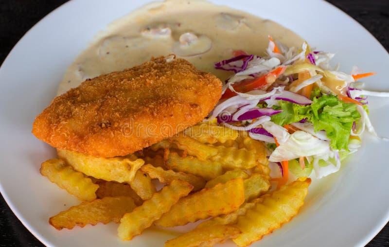 Escalope de veau avec la pomme de terre et la salade du plat blanc Photo de vue supérieure de côtelette de poulet frit sur la tab photo stock