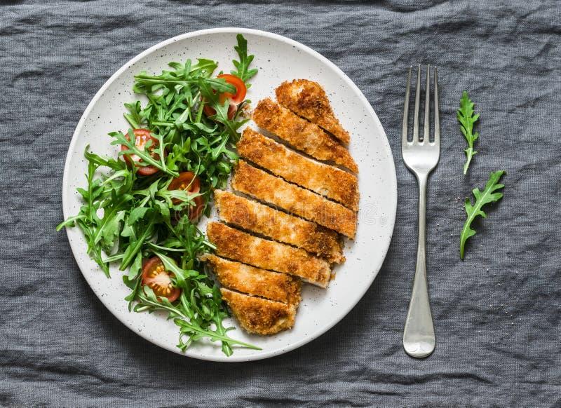 Escalope de veau traditionnelle de poulet avec de la salade de tomates-cerises d'arugula sur le fond gris image stock