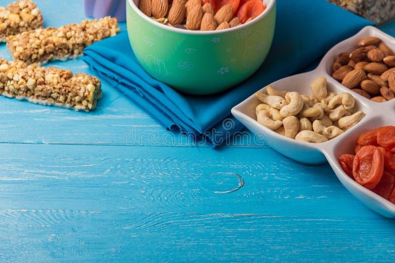 Escamas con frutos secos, nueces del cereal del Granola en cuenco verde en la tabla de madera azul con el copyspace foto de archivo