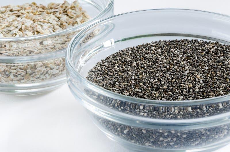 Escamas de la avena y semillas del chia en un bol de vidrio fotografía de archivo libre de regalías