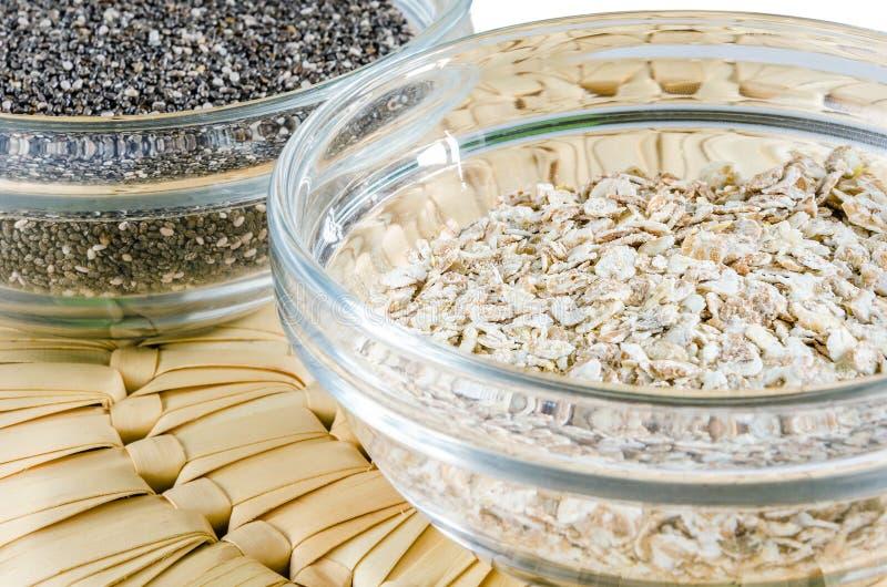 Escamas de la avena y semillas del chia en un bol de vidrio imagen de archivo