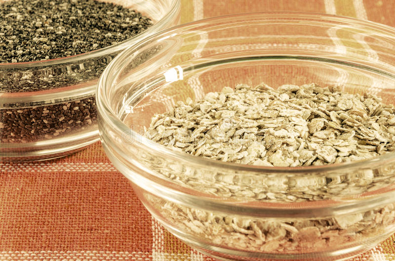 Escamas de la avena y semillas del chia en un bol de vidrio imágenes de archivo libres de regalías