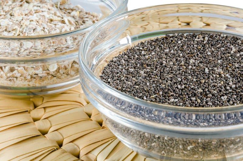 Escamas de la avena y semillas del chia en un bol de vidrio fotografía de archivo